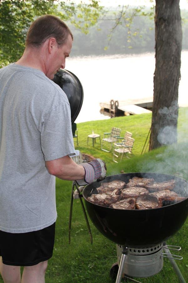 Стейки приготовления на гриле человека для 4-ого из пикника праздника в июле стоковое изображение