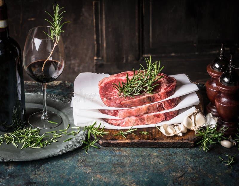 Стейки с травами и специями и красным вином на постаретых кухонных столах, варя подготовку стоковые изображения