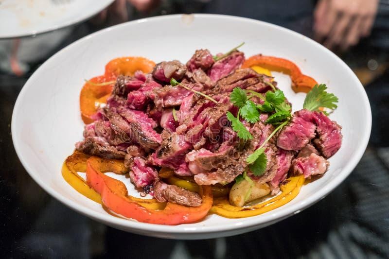 Стейк говядины отрезанный с томатом и картошкой на белой плите стоковая фотография rf