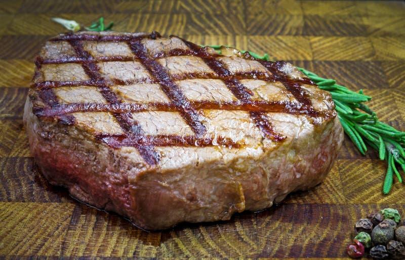 Стейк говядины с розмариновым маслом хворостины на деревянном столе стоковая фотография rf