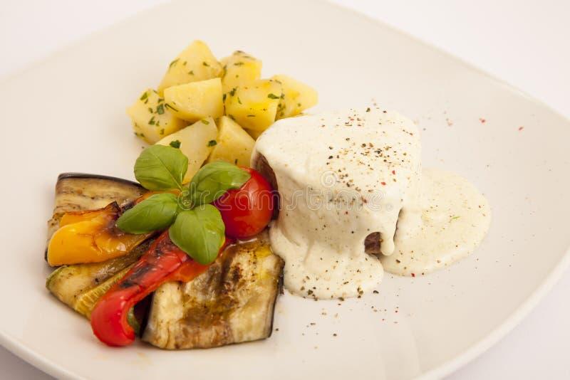 Стейк говядины на хлебе с соусом, зажаренными овощами и картошкой стоковые изображения rf