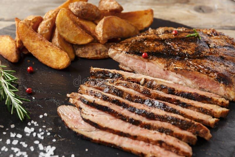 Стейк говядины отрезанный с испеченными картошкой и соусом стоковые фото