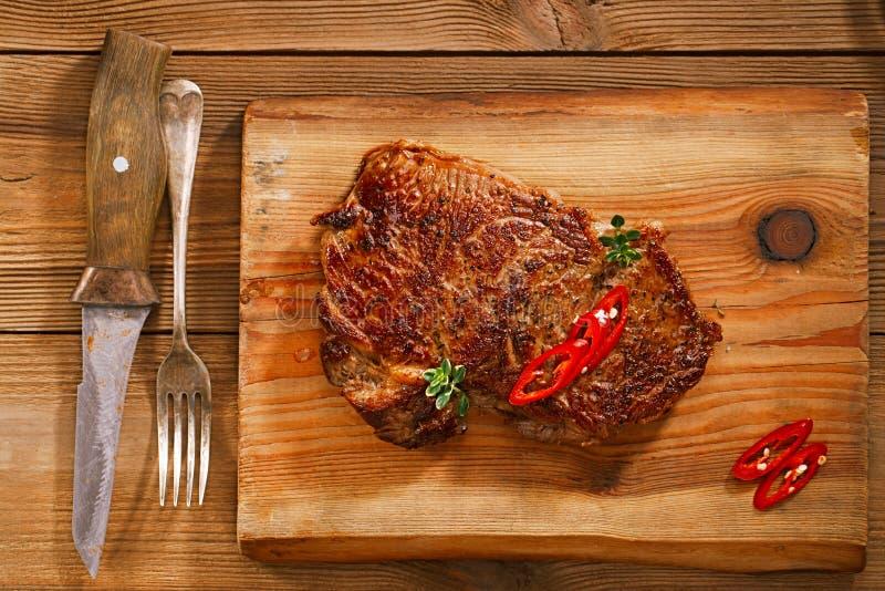 Стейк говядины с красными чилями на древесине и таблице стоковые изображения