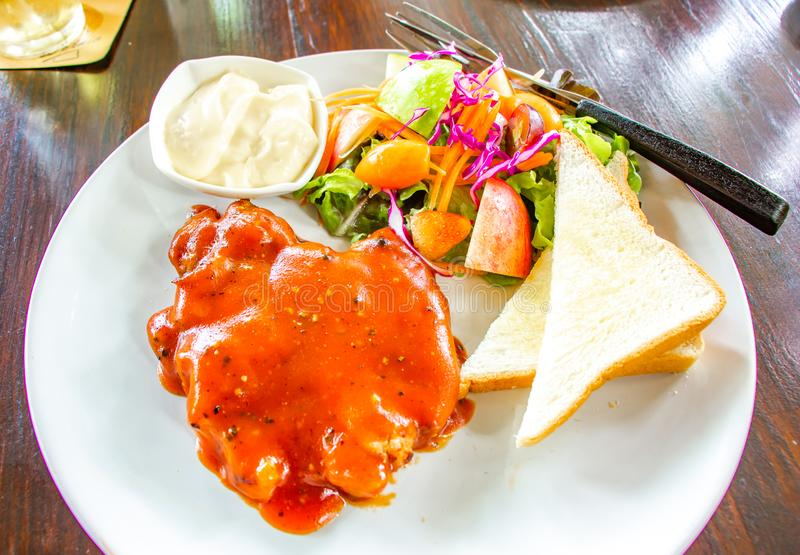 Стейк зажаренной в духовке свинины взгляда сверху или зажаренный стейк свинины с овощами салата на блюде стоковые фотографии rf