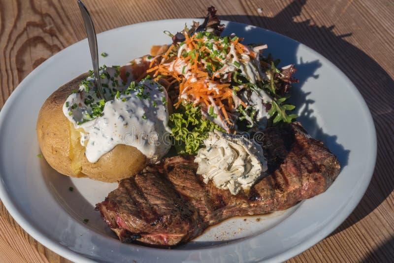 Стейк, картошка куртки и салат стоковое изображение rf