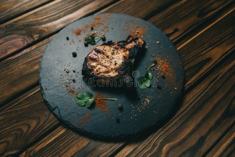 Стейк косточки свинины на деревянной предпосылке с медом Шифер доски kenza, перец стоковое фото