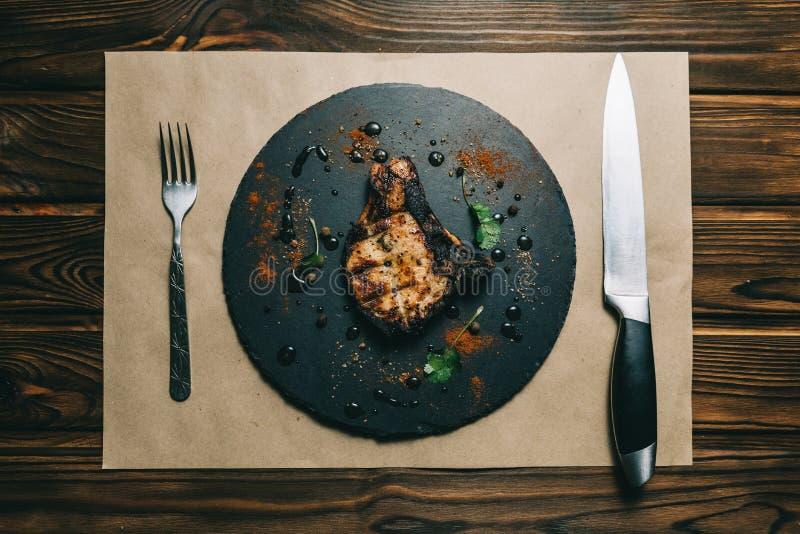 Стейк косточки свинины на предпосылке доски деревянной с медом kenzy, перцем стоковое фото rf