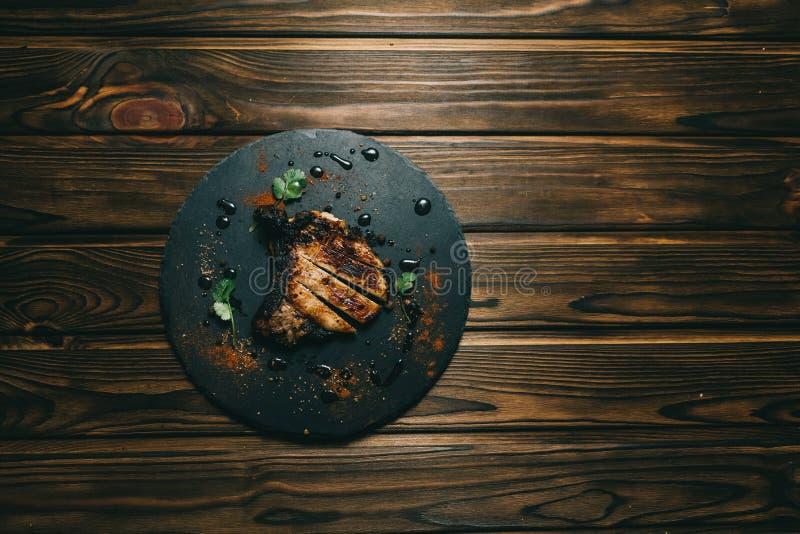 Стейк косточки свинины на предпосылке доски деревянной с медом kenzy, перцем стоковые фотографии rf
