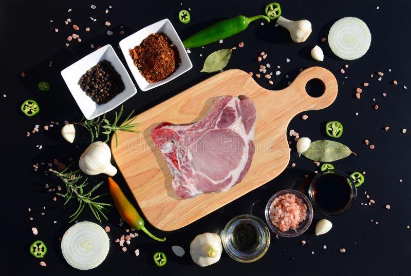 Стейк мяса на разделочной доске и перце, лист залива, розмариновом масле, луках, соли, оливковом масле, соевом соусе стоковое изображение