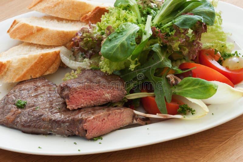 Стейк оковалка с салатом стоковое изображение