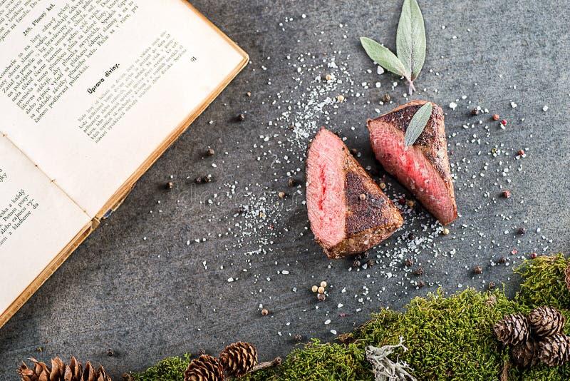 Стейк оленей или оленины с ингридиентами любит соль моря, травы и книга перца и кашевара, предпосылка еды для ресторана или lo зв стоковое фото