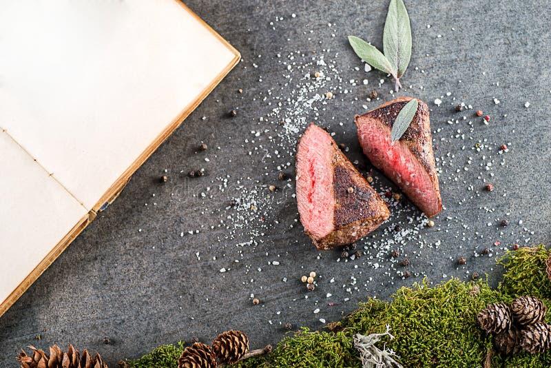 Стейк оленей или оленины с ингридиентами любит соль моря, травы и книга перца и кашевара, предпосылка еды для ресторана или lo зв стоковое изображение
