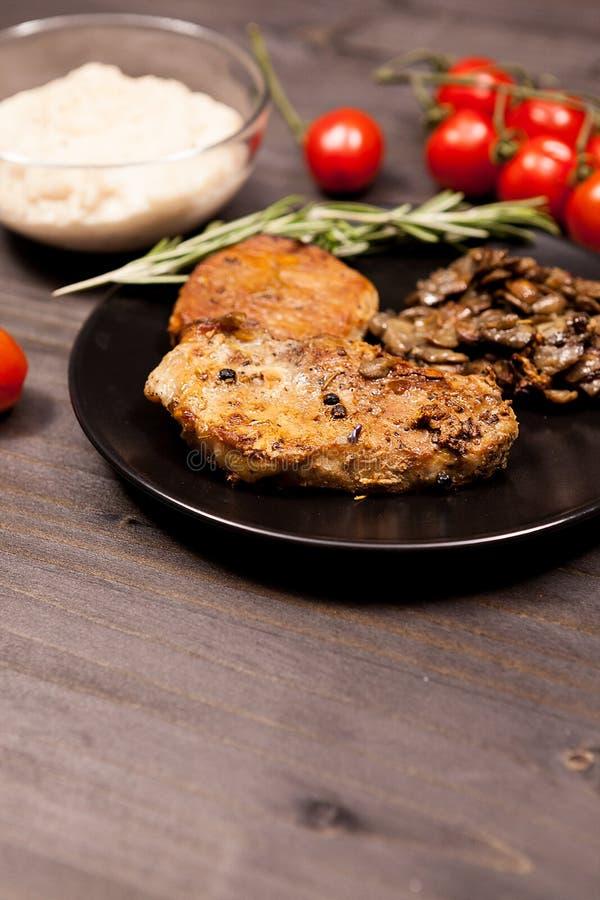 Стейк свинины в черной плите с зажаренными грибами, вишне душицы стоковая фотография