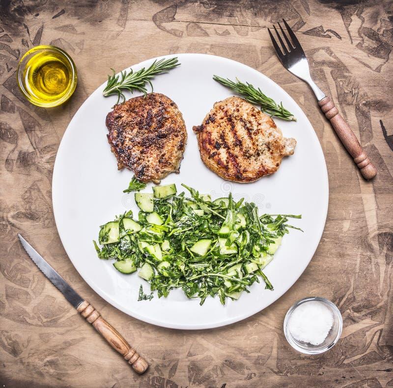 Стейк свинины здоровой еды аппетитный зажаренный с зеленым салатом плиты огурца, шпината и arugula белой на деревянном деревенско стоковые изображения
