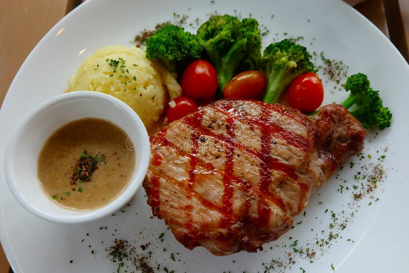 Стейк свинины, который служат с брокколи и картофельными пюре стоковое фото