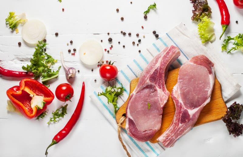 Стейк свинины 2 с мясом и свежими специями приправой на белой деревянной предпосылке, взгляд сверху стоковое фото