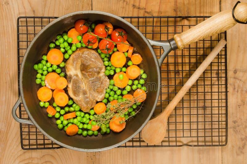 Стейк шеи свинины с горохами и морковами в лотке литого железа стоковое фото