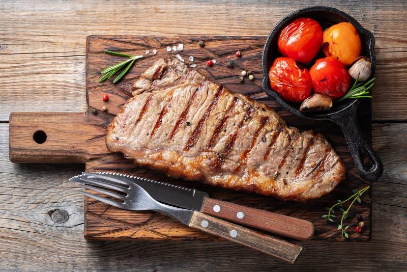 Стейк Striploin, зажаренное с перцем, чеснок, соль и тимиан служил на деревянной доске Законченное блюдо для обедающего на старой стоковое фото rf