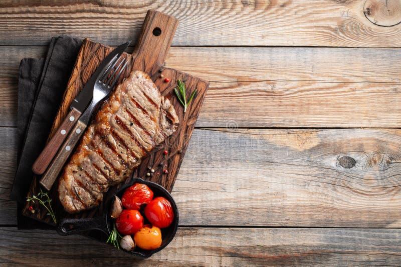 Стейк Striploin, зажаренное с перцем, чеснок, соль и тимиан служил на деревянной доске Законченное блюдо для обедающего на старой стоковые изображения rf