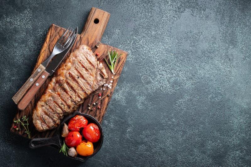 Стейк Striploin, зажаренное с перцем, чеснок, соль и тимиан служил на деревянной доске Законченное блюдо для обедающего на темнот стоковые изображения rf