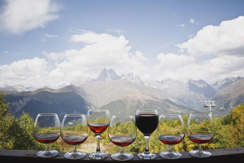 5 стекел коньяка и 2 стекел стойки красного и розового вина против фона красивых ландшафта горы и кабеля c стоковые изображения