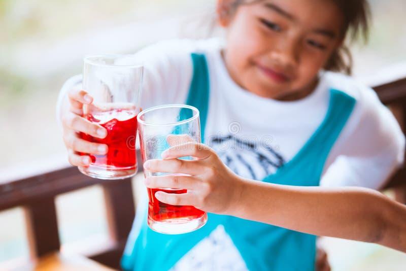 2 стекла азиатских девушки ребенка clinking свежей красной воды сока стоковые изображения rf