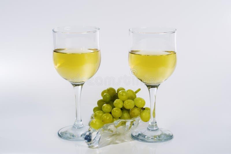 2 стекла белого вина и пука зеленых виноградин на стеклянной пластинке стоковое изображение
