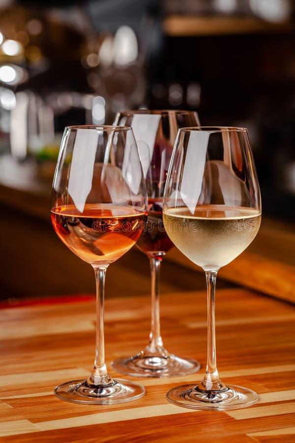 Стекла белого, розового и красного вина на таблице, бутылке и пробочки близрасположенны Стекла на таблице в баре стоковая фотография
