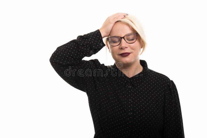 Стекла белокурой учительницы нося показывая жест головной боли стоковые фото
