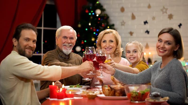 Стекла большой дружелюбной семьи clinking с вином на кануне Xmas, смотря в камеру стоковые изображения rf
