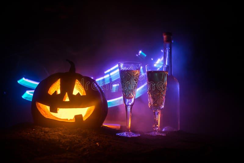 2 стекла вина и бутылки с хеллоуином - старого Джек-o-фонарика на темной тонизированной туманной предпосылке тыква halloween стра стоковое изображение rf