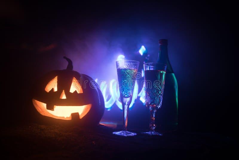 2 стекла вина и бутылки с хеллоуином - старого Джек-o-фонарика на темной тонизированной туманной предпосылке тыква halloween стра стоковые изображения rf
