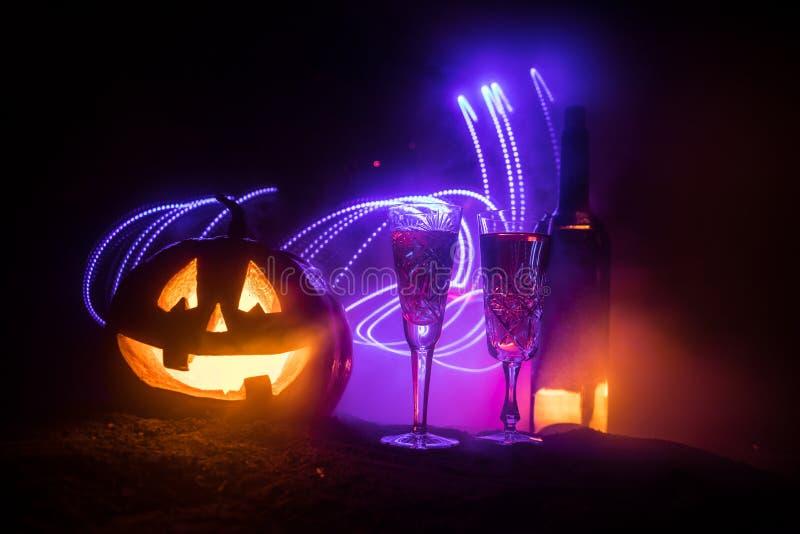 2 стекла вина и бутылки с хеллоуином - старого Джек-o-фонарика на темной тонизированной туманной предпосылке Страшная тыква хелло стоковые фото