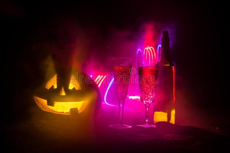 2 стекла вина и бутылки с хеллоуином - старого Джек-o-фонарика на темной тонизированной туманной предпосылке Страшная тыква хелло стоковые изображения