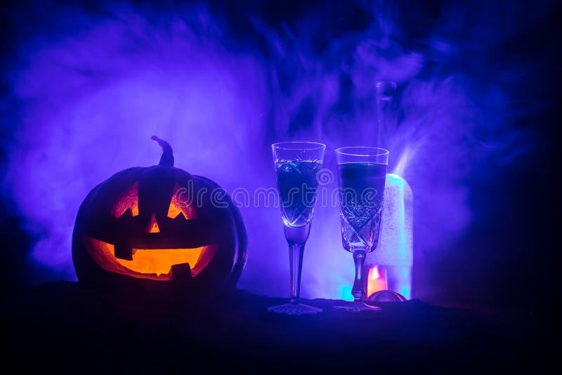 2 стекла вина и бутылки с хеллоуином - старого Джек-o-фонарика на темной тонизированной туманной предпосылке Страшная тыква хелло стоковое фото
