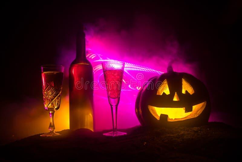 2 стекла вина и бутылки с хеллоуином - старого Джек-o-фонарика на темной тонизированной туманной предпосылке Страшная тыква хелло стоковая фотография rf