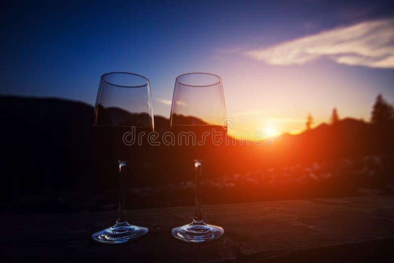 2 стекла вина на небе захода солнца драматическом на предпосылке ландшафта горы стоковые изображения