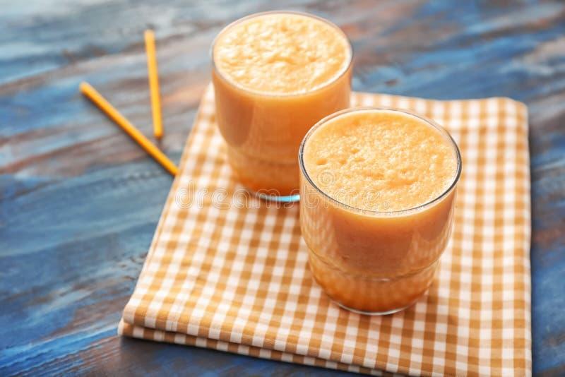 Стекла вкусного smoothie дыни на деревянном столе стоковое фото rf