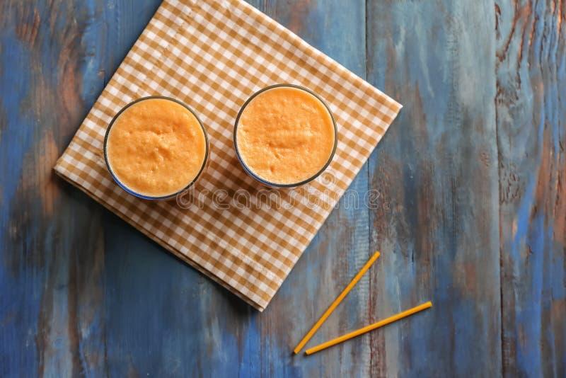 Стекла вкусного smoothie дыни на деревянном столе стоковое изображение rf