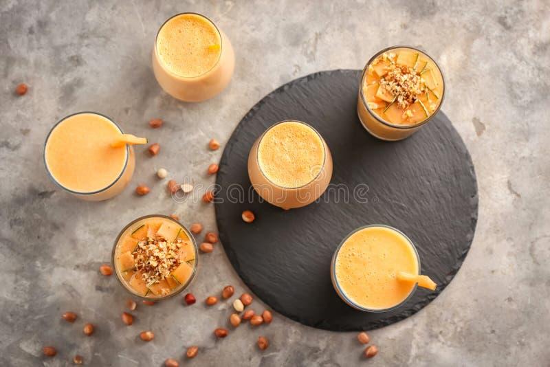 Стекла вкусного smoothie дыни на серой таблице стоковое изображение rf