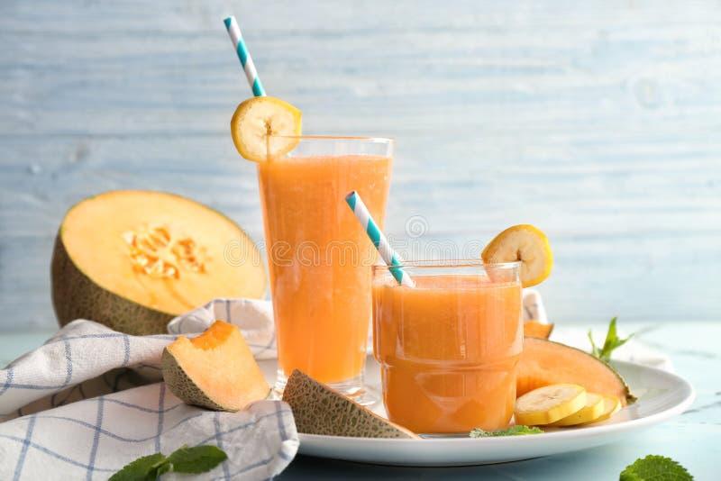Стекла вкусного smoothie дыни на таблице стоковые изображения rf