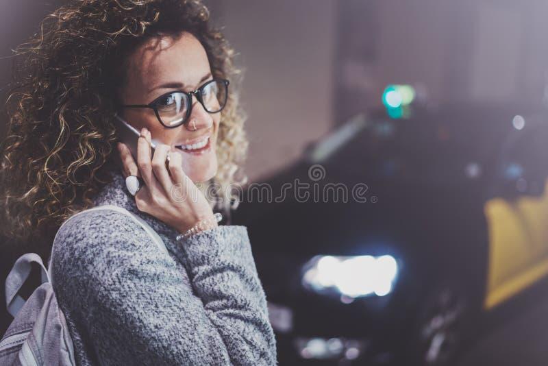 Стекла глаза туриста женщины нося вызывая обслуживание такси телефоном клетки, пока стоит на улице в ноче стоковые фотографии rf