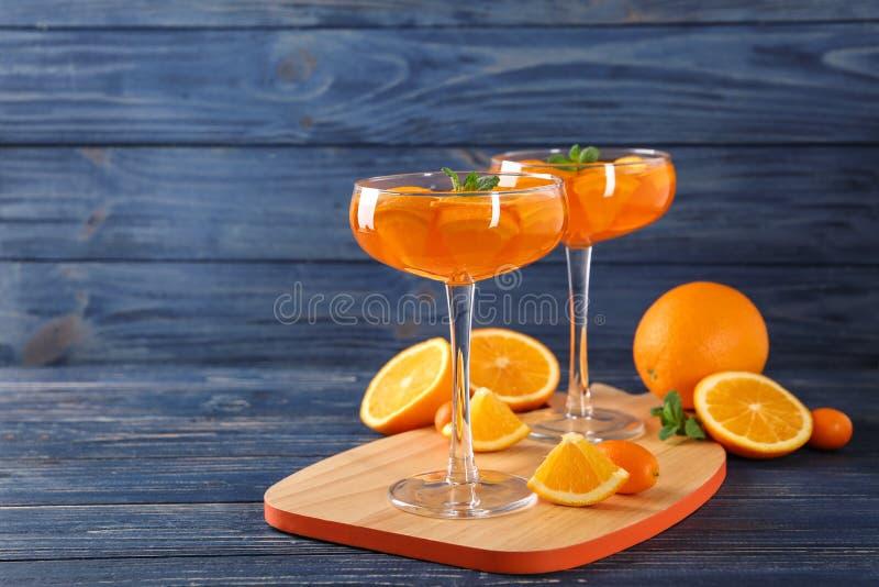 Стекла десерта оранжевого студня, который служат на голубом деревянном столе стоковые изображения