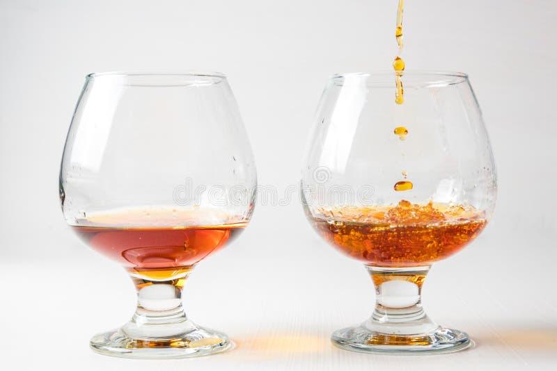 2 стекла для коньяка с вискиом с различной брызгают стоковые фотографии rf