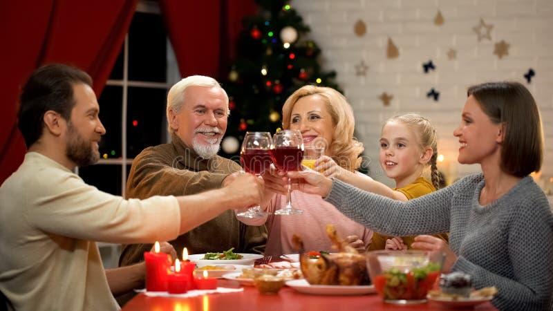 Стекла дружелюбной семьи clinking с вином на кануне Xmas, деревом блестящим позади стоковая фотография