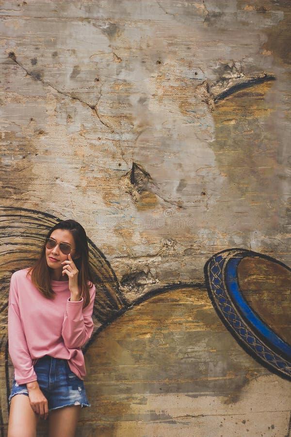 Стекла женщины нося стоя около старой стены стоковое фото