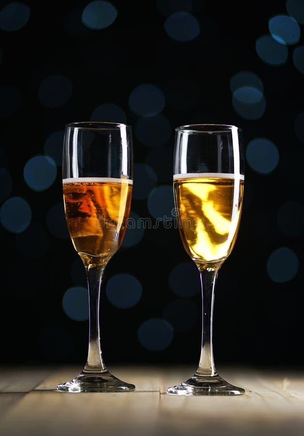 2 стекла зарева Шампани темного освещают предпосылку стоковое изображение