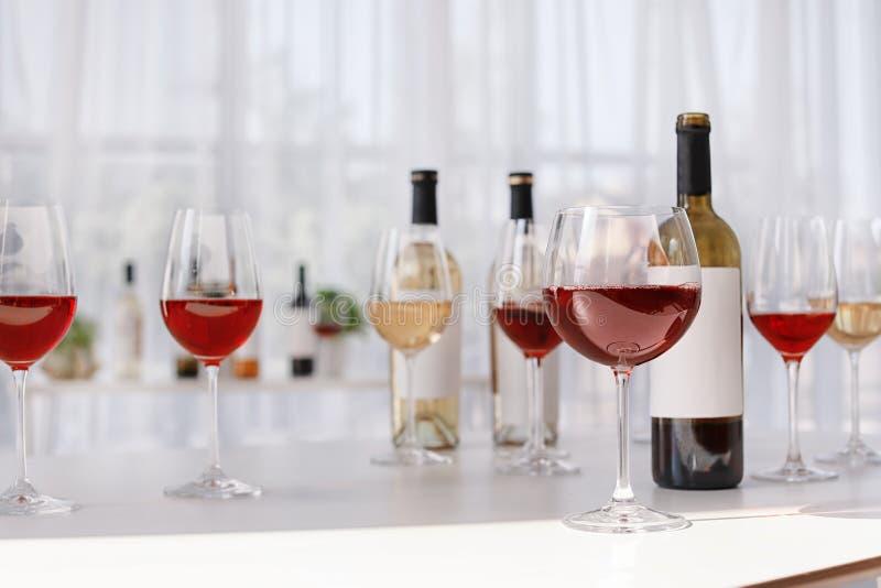 Стекла и бутылки с очень вкусным вином на таблице стоковое фото rf