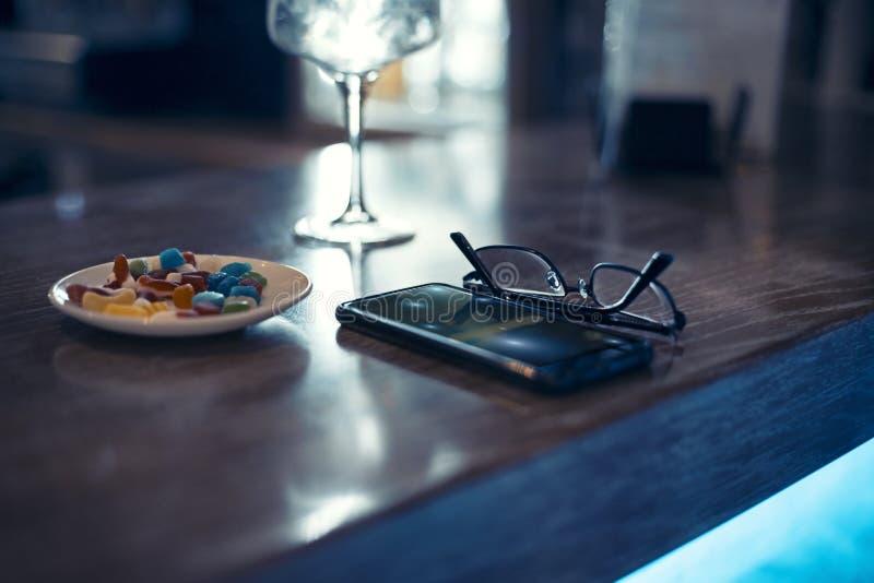 Стекла и смартфон в баре вечером стоковая фотография