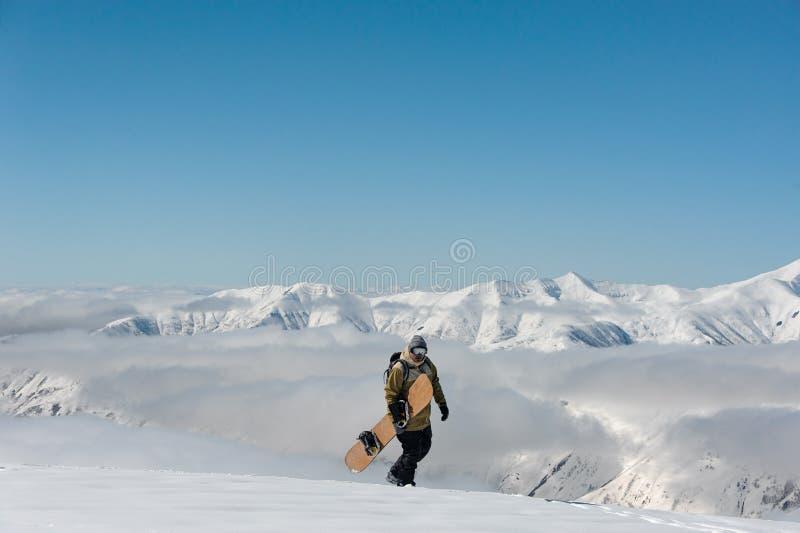 Стекла и сноуборд мужчины нося идя в снег против фона гор стоковое фото rf